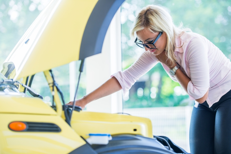 Woman with glasses checking car engine