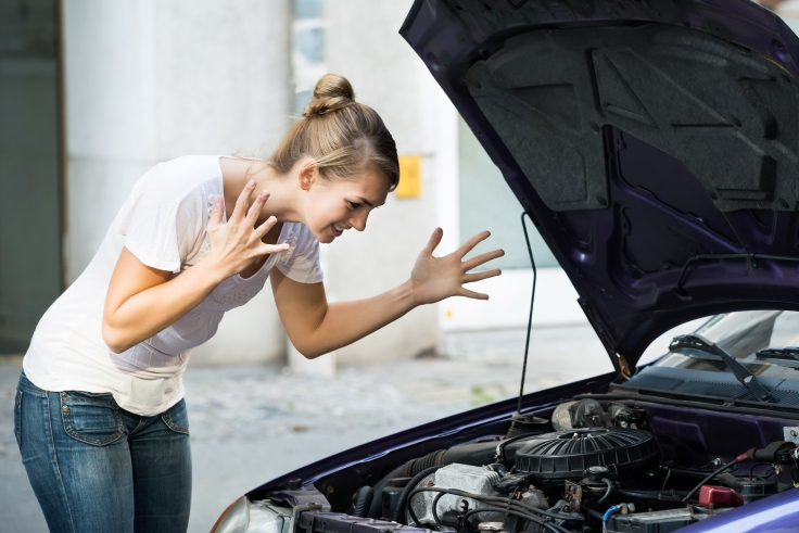 Frustrated Woman Looking At Broken Down Car Engine